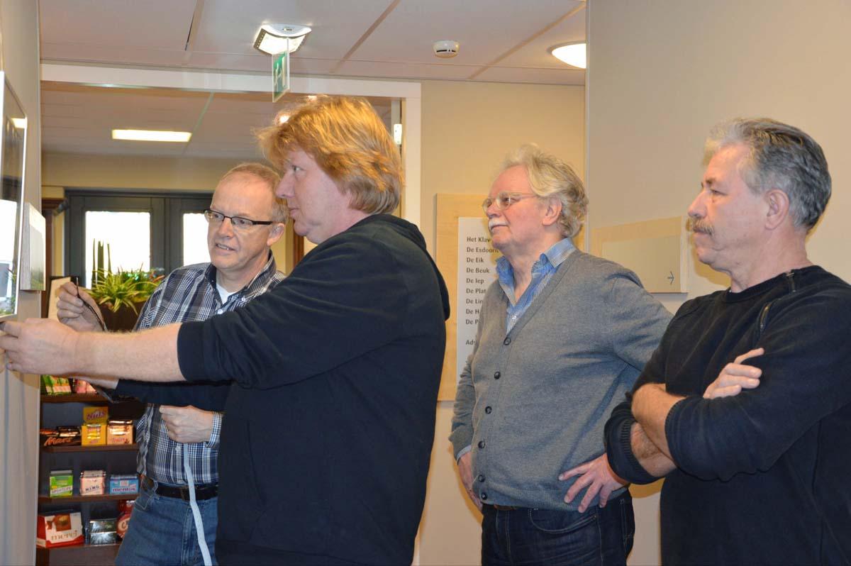 """V.l.n.r. Ton van Vroonhoven, Ivo Scholten, Wim Peters en Ton Nijhuis van de fotokring verzorgen de """"finishing touch"""" bij het inrichten van de tentoonstelling."""